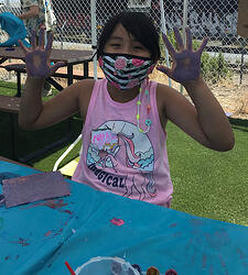 Camper with paint on her hands