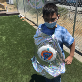 A camper with their cape and shield