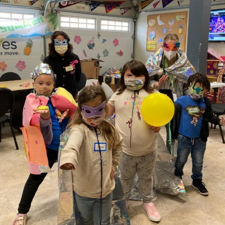 Campers in masks and capes