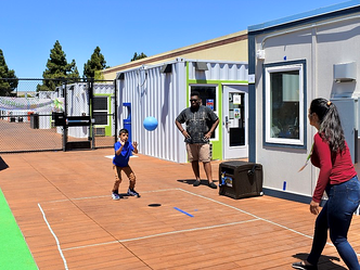 Camper and staff playing four square